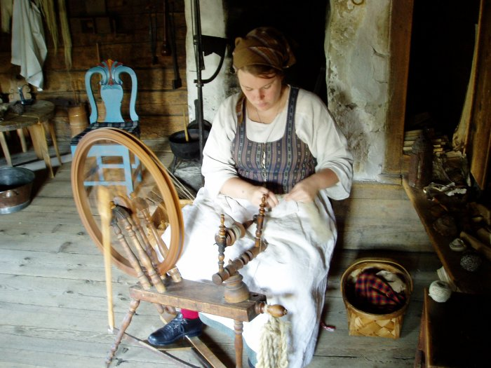 A Skansen docent demonstrates the craft of spinning yarn
